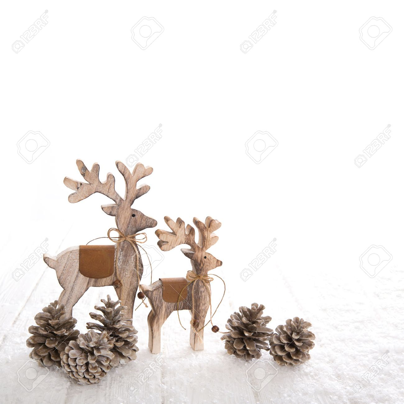 Couple of thw wooden deer with fir cone on white wooden background. Banque d'images - 47341496