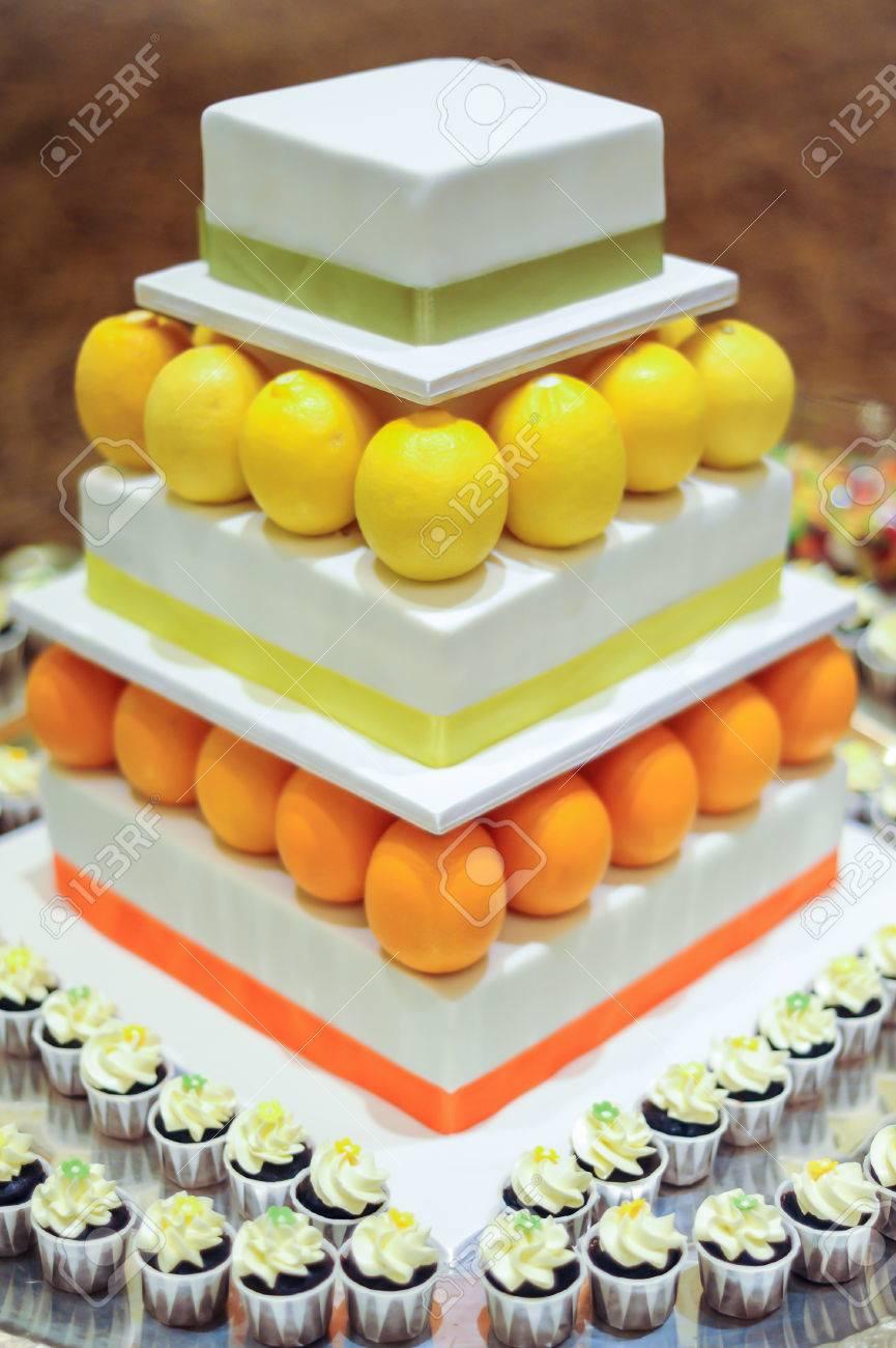 Orange Lemon 3 Tier White Wedding Cake With Mini Cupcakes Stock ...