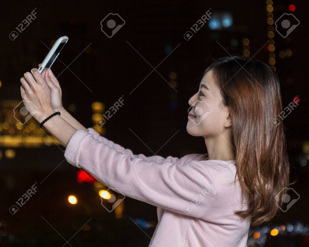 Beautiful Malaysian female with bright lights of city in background - 25019900
