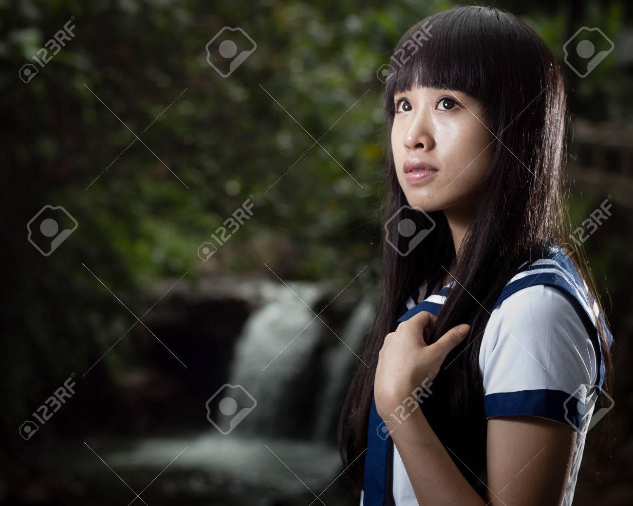 バック グラウンドで滝かわいい中国の女子高生 ロイヤリティーフリー