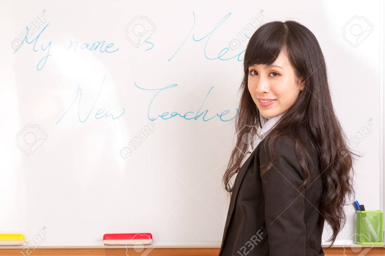 Chinese female teacher writing name on whiteboard for first day