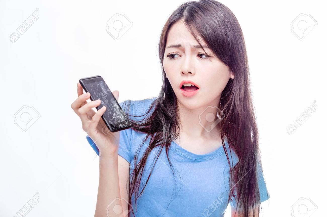 Asian woman looking at broken smartphone in disbelief - 47687908