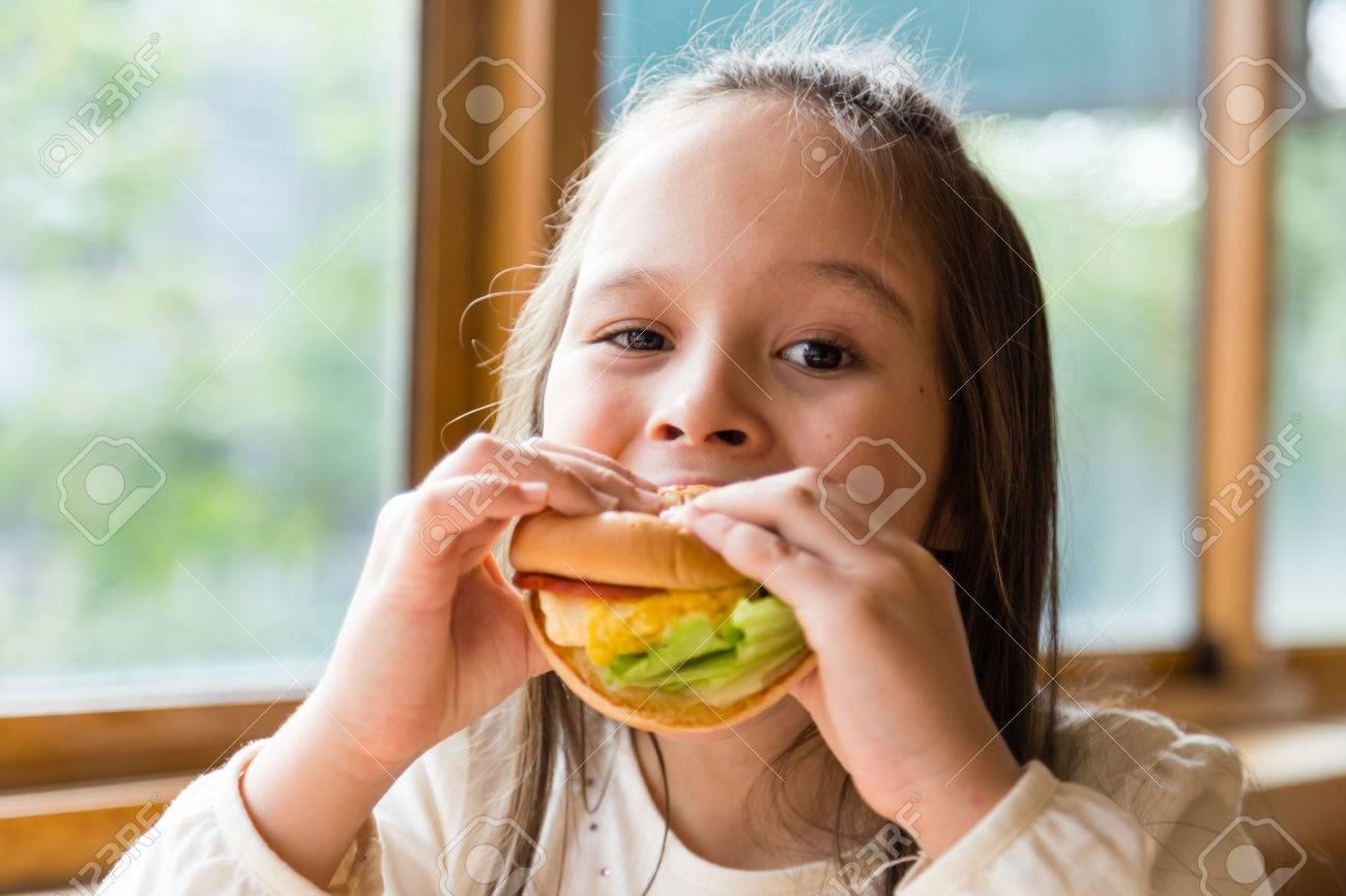 Asian American girl eating burger - 50477295