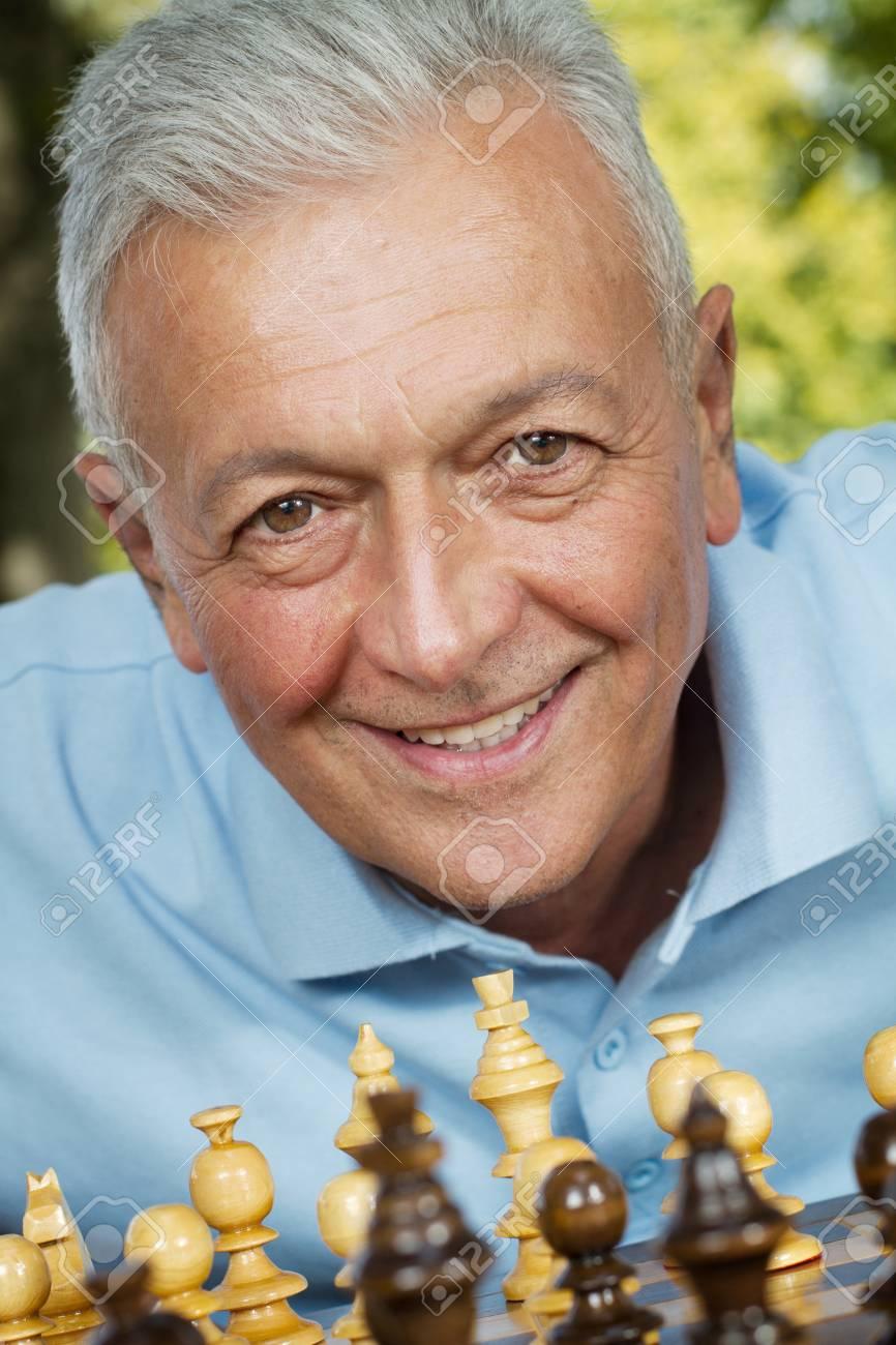 Handsome senior enjoys chess game outdoors Stock Photo - 13686875