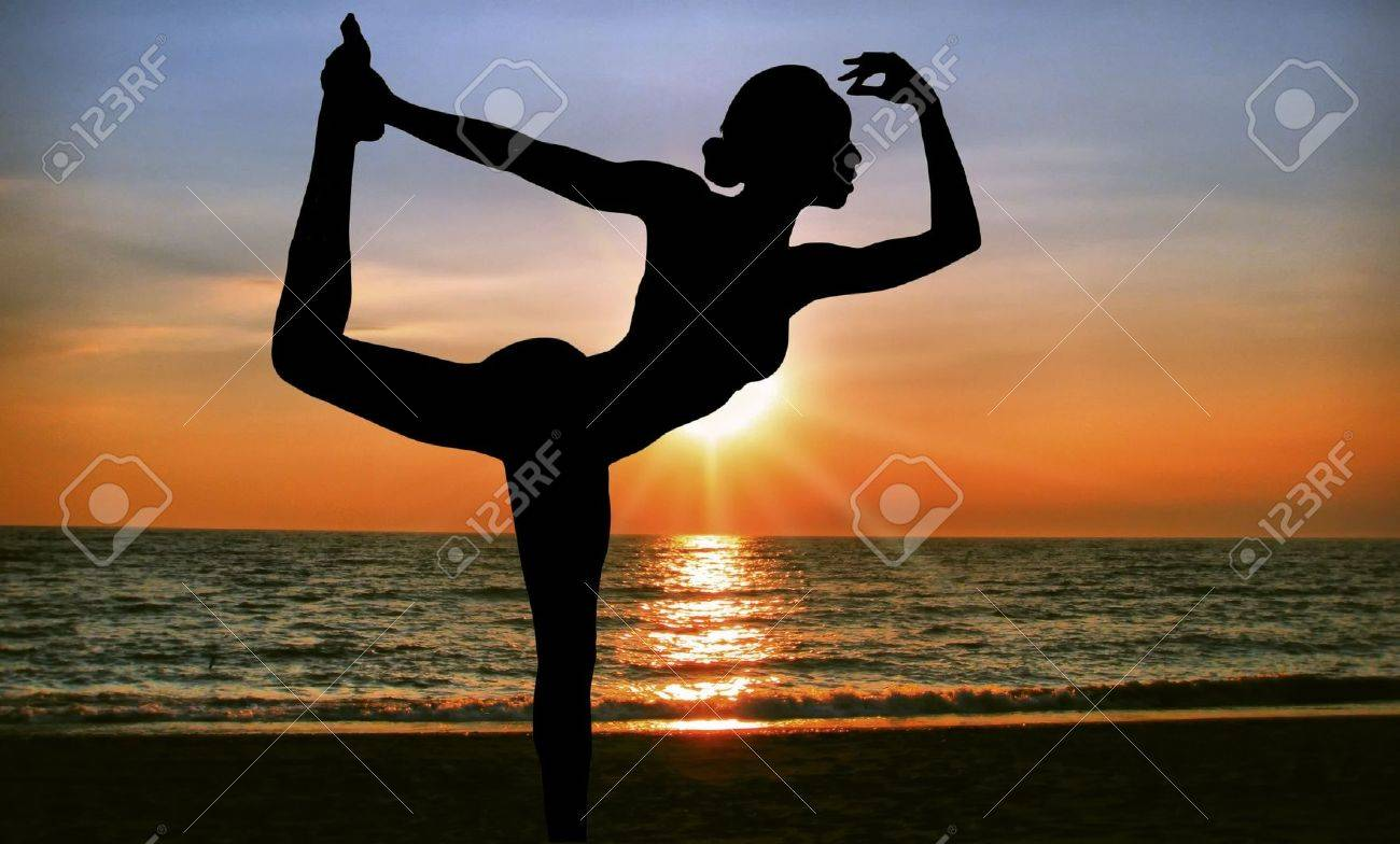 practicing yoga at sunrise on the beach Stock Photo - 6359116