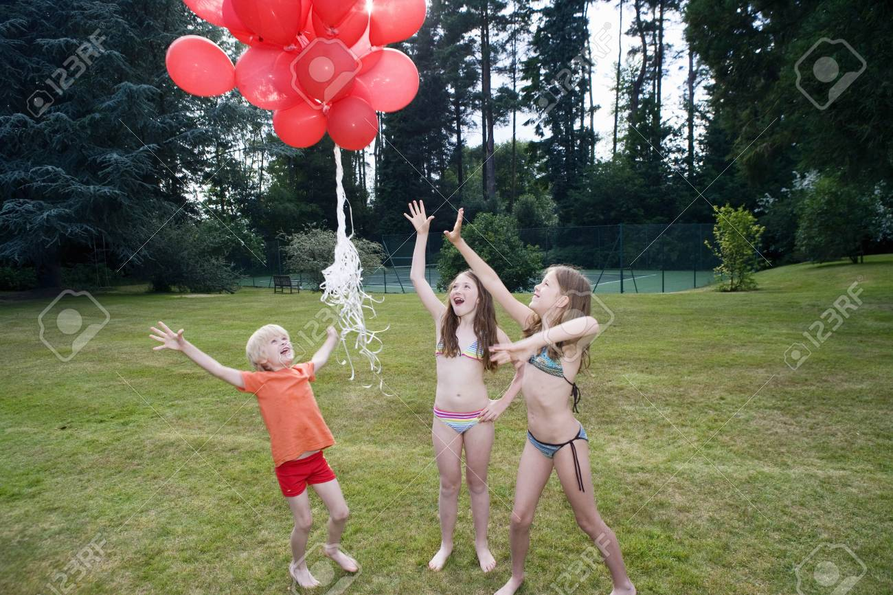 Kids letting red balloons go - 104950369