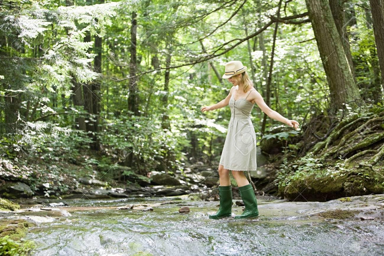 Woman walking in river - 86036190