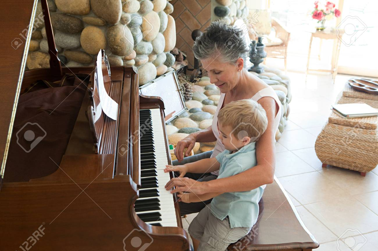 Grandmother and grandson playing the piano - 86036680