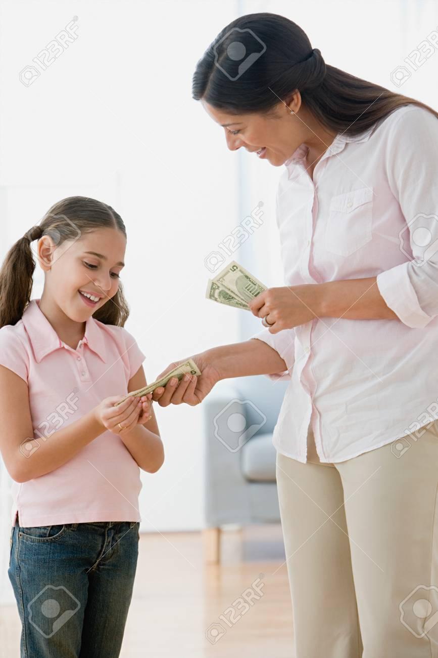 Mother giving daughter pocket money - 86037257