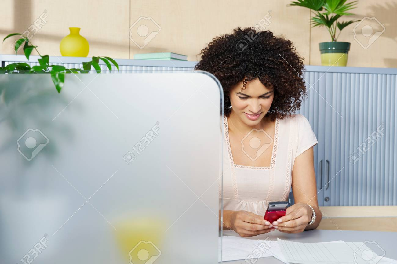 Young woman at desk with mobile phone - 114005546
