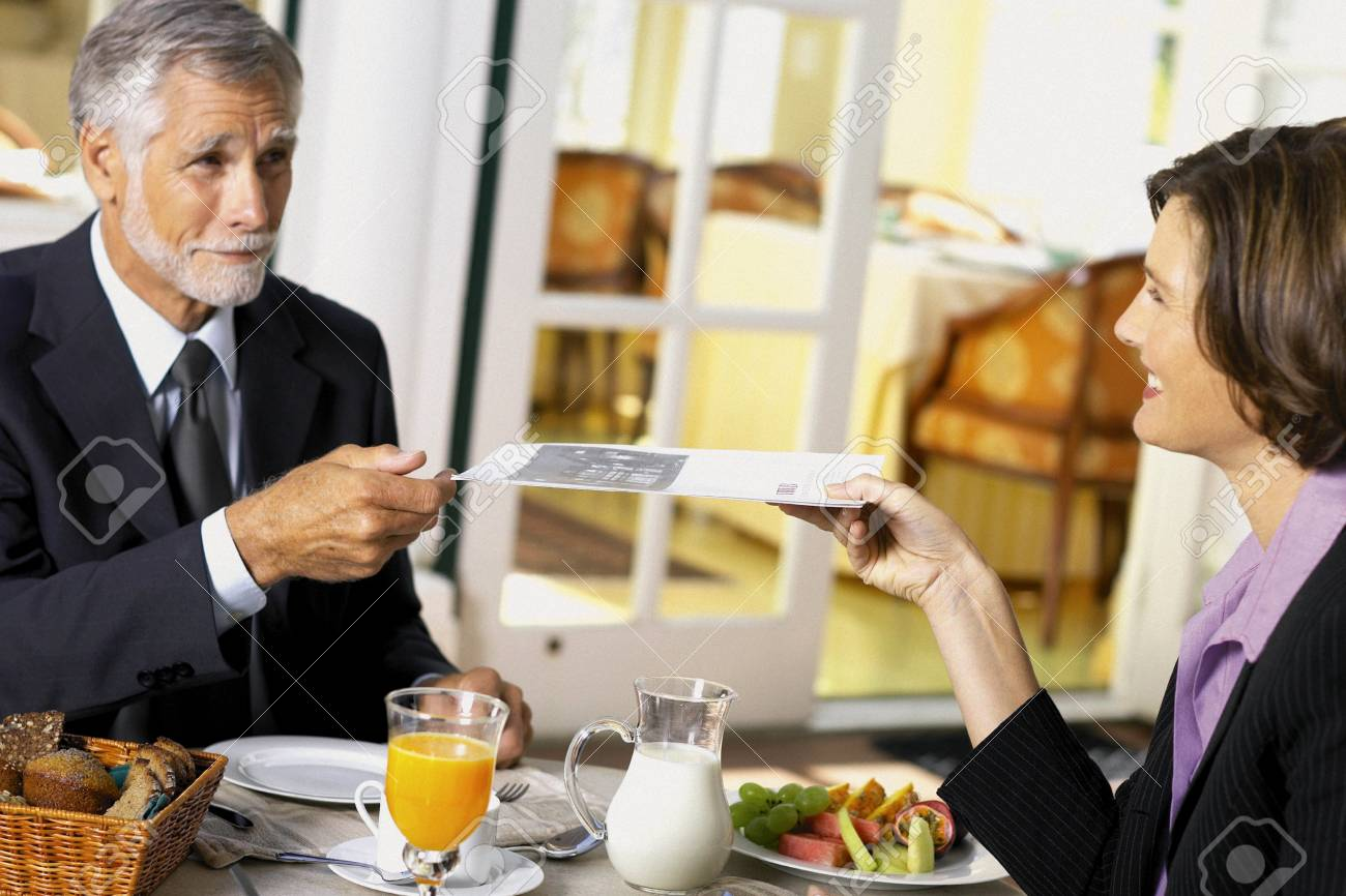 Businessman and businesswoman conducting business over breakfast - 116728239