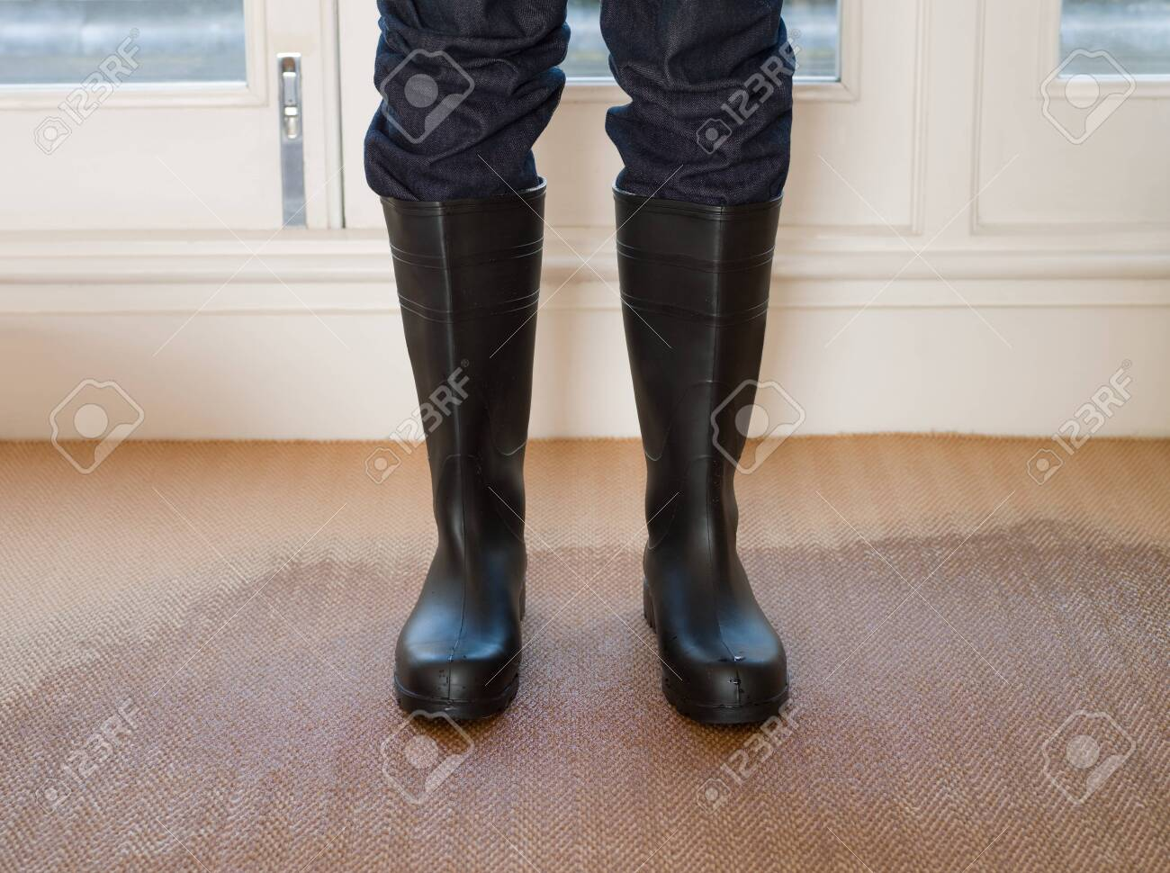 Person wearing rubber boots on a wet carpet - 129131422