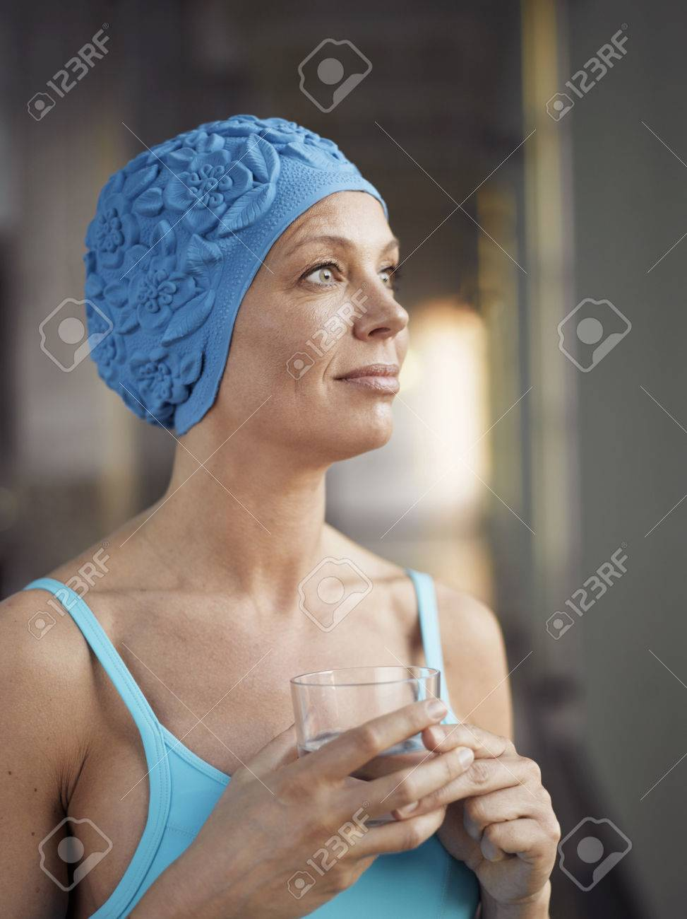 Mature woman wearing bathing suit, holding glass of water Stock Photo -  80207004