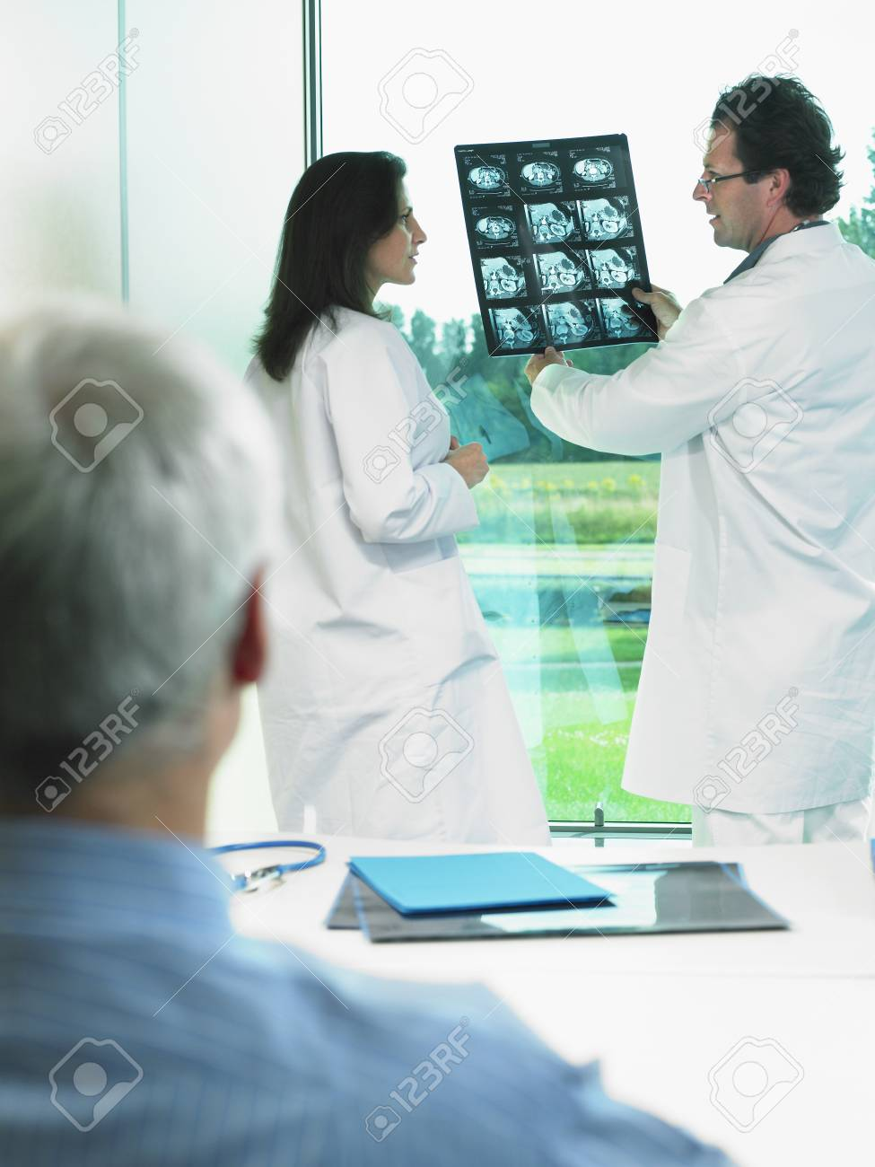 two doctors discussing x-rays with mature patient. stock photo