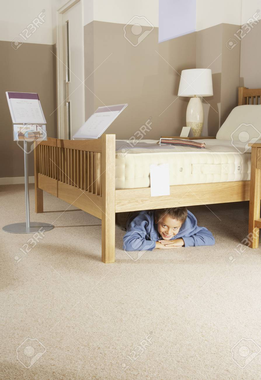Boy Hiding Under Bed In Furniture Store Stock Photo Picture And
