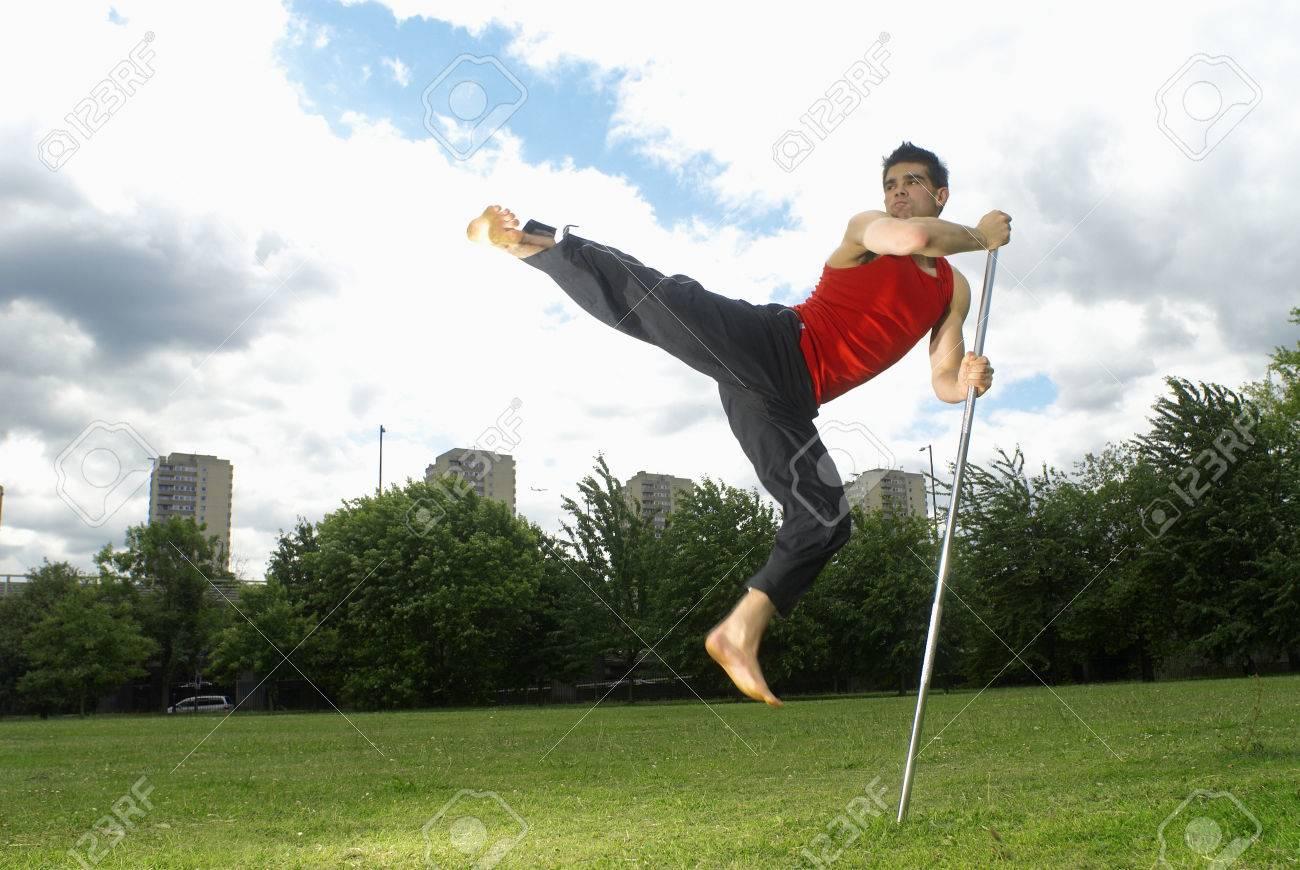 man jumping using bow staff