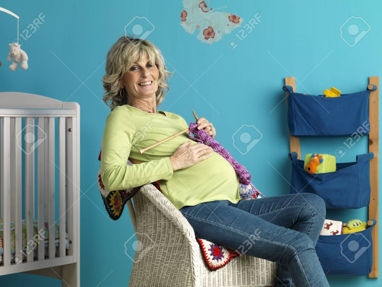 pregnant mature woman knitting stock photo, picture and royalty free