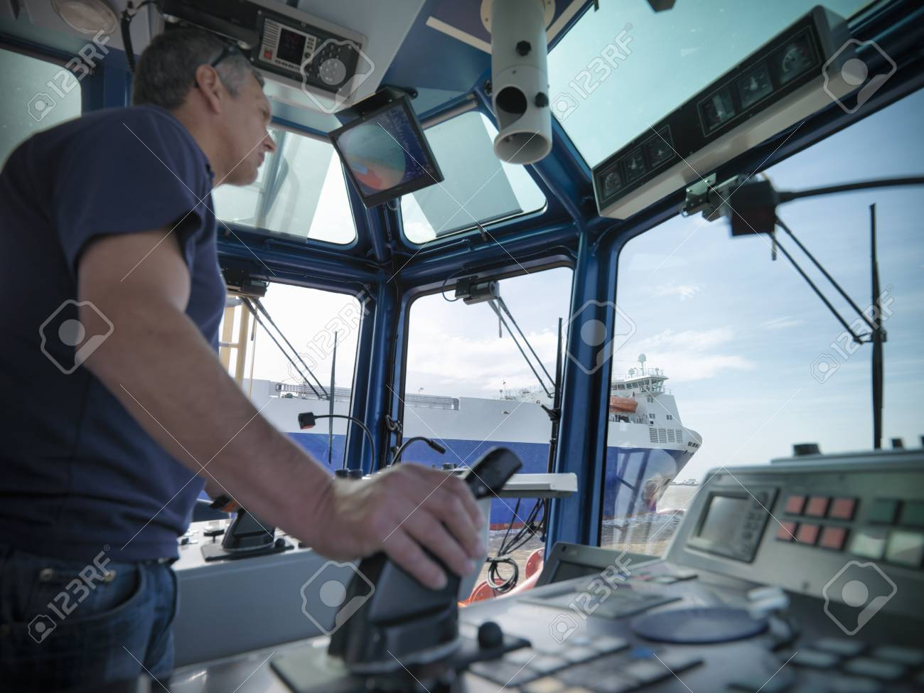 Tugboat captain steering in wheelhouse