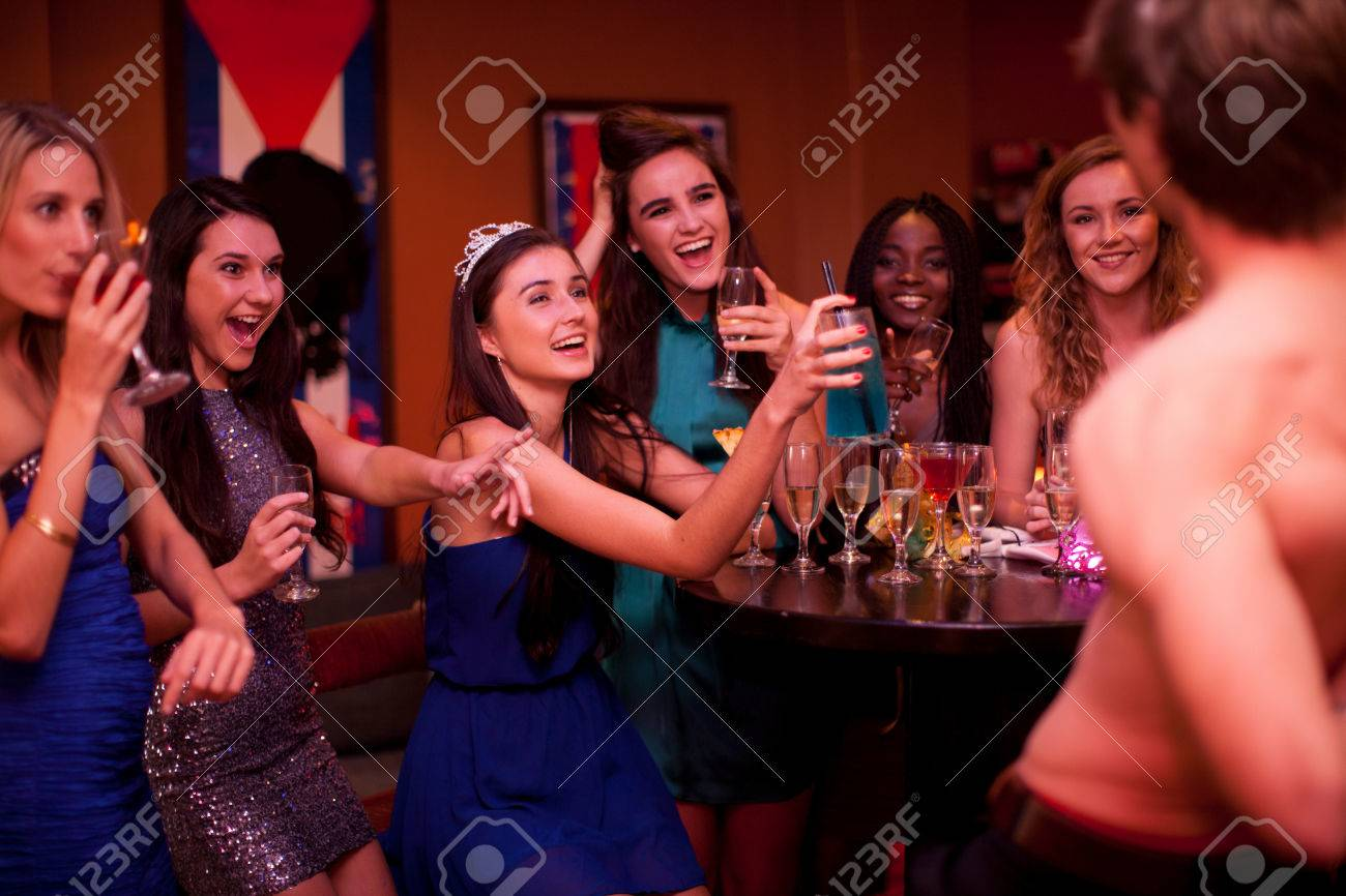 Stock Photo - Young women watching male stripper at hen party