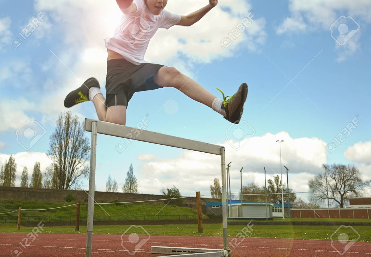 Boy Jumping Over Hurdle On Track Stock Photo