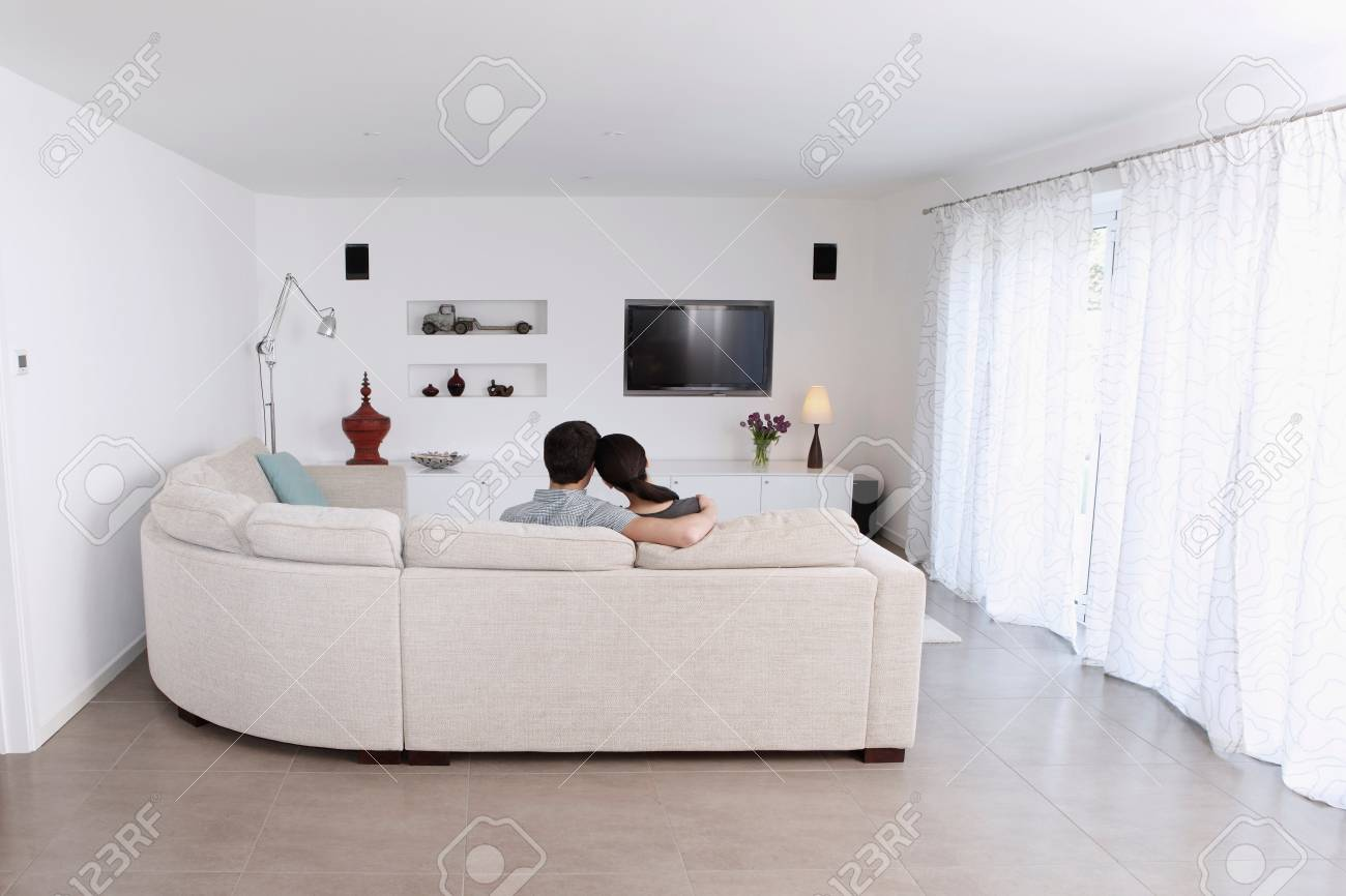 Husband And Wife Relaxing On Corner Sofa In Living Room Stock Photo ...