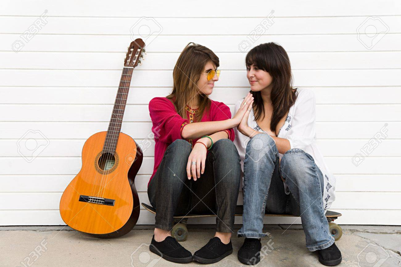 two girls sitting on floor with guitar stock photo picture and