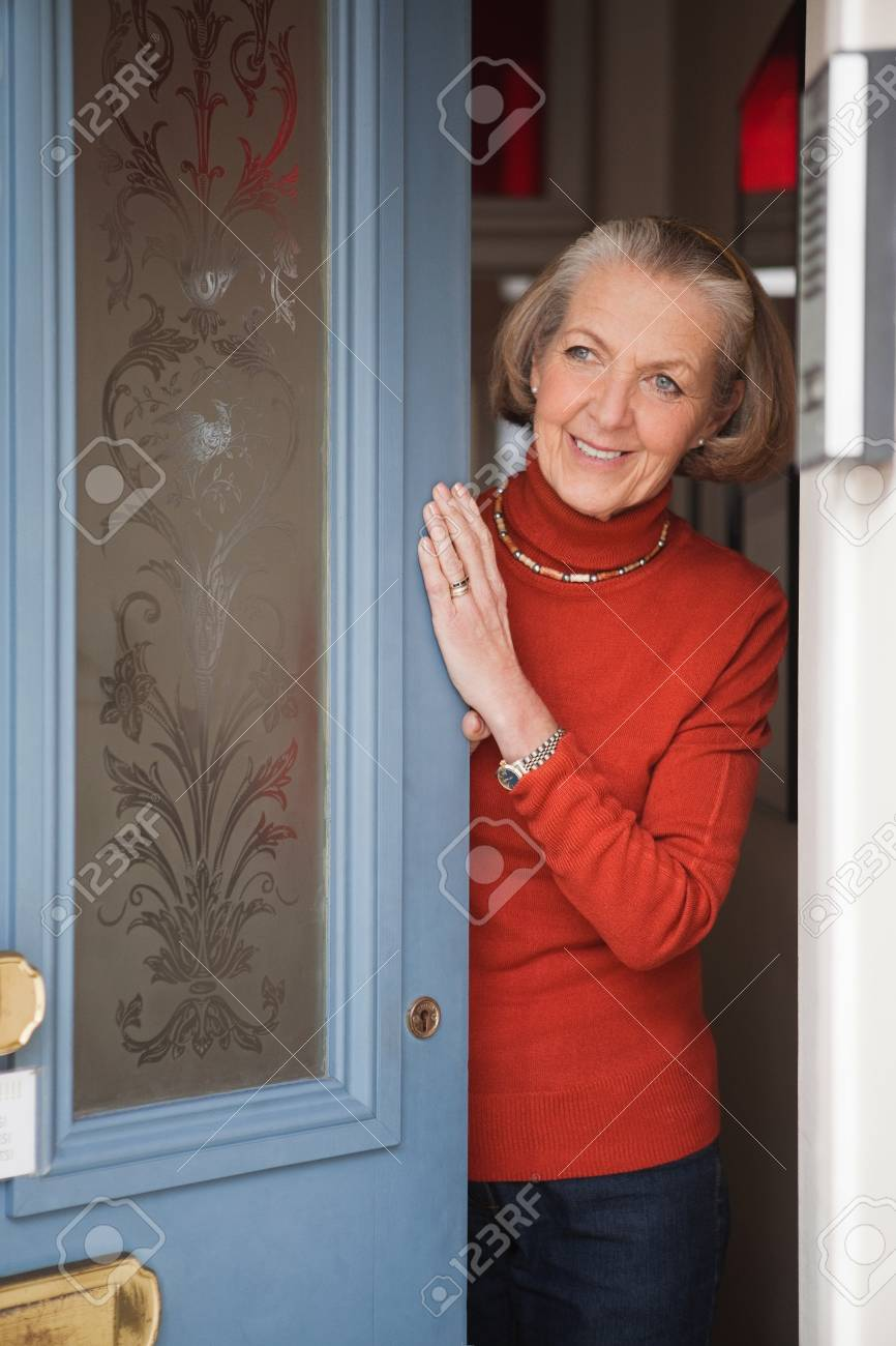 opening front door. Senior Woman Opening Front Door Stock Photo - 82294640