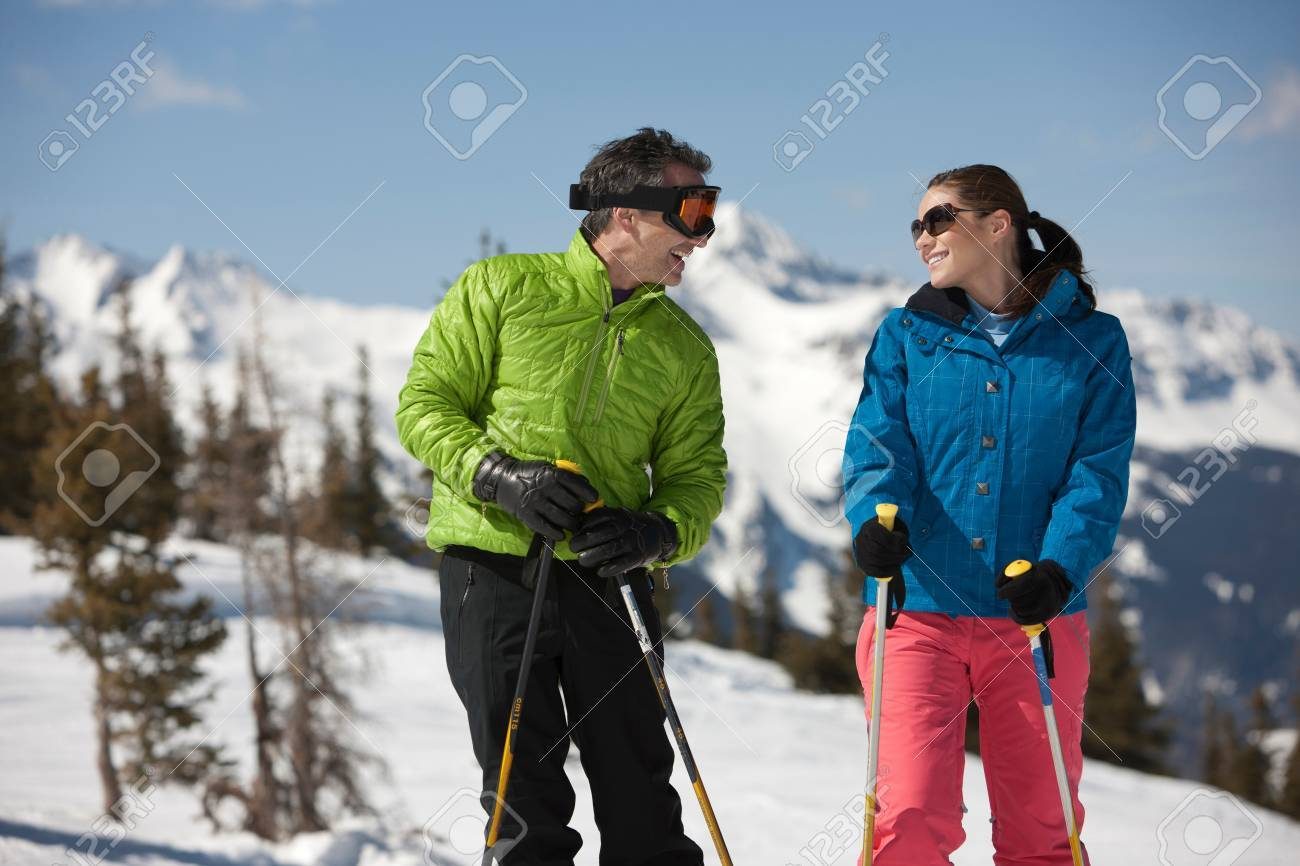 Stock Photo - Young woman and mature man in skiwear holding ski poles