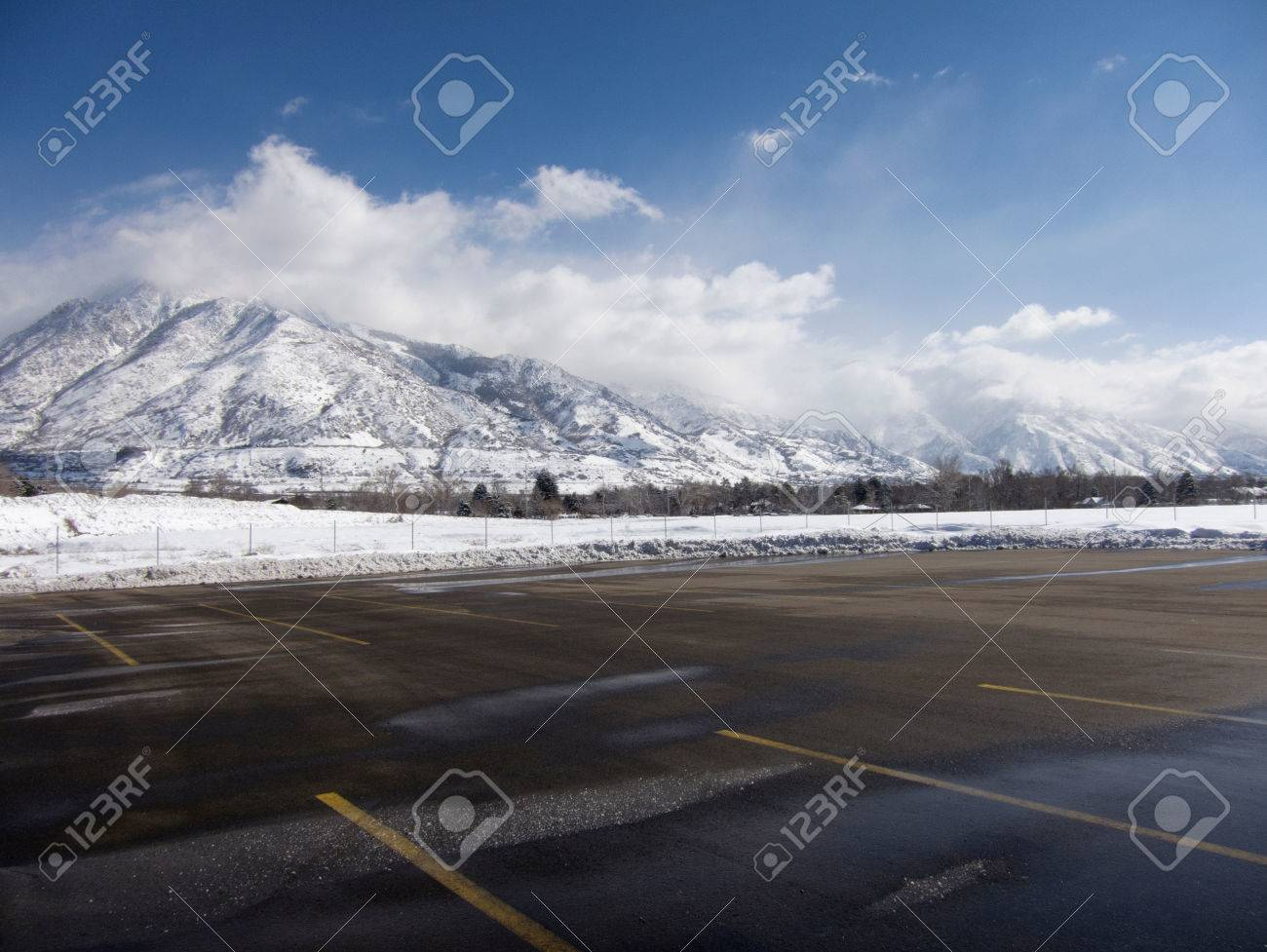Empty Parking Lot With Snow Covered Wasatch Mountains In Background Salt