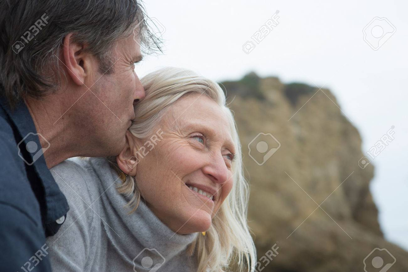 mature man kissing mature woman's head,close-up stock photo, picture