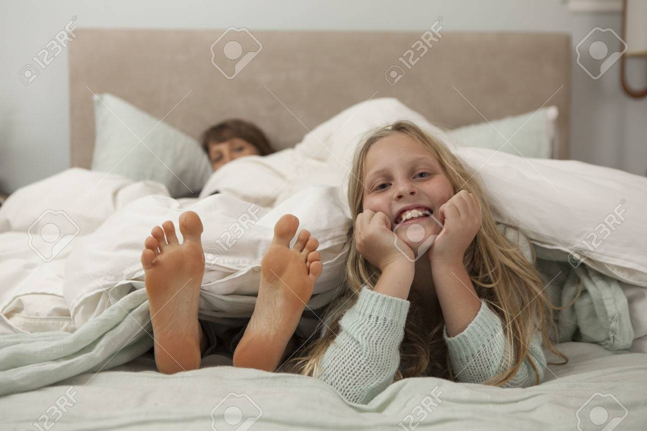 girl feet Portrait of girl lying on bed with mothers feet Stock Photo - 81326502