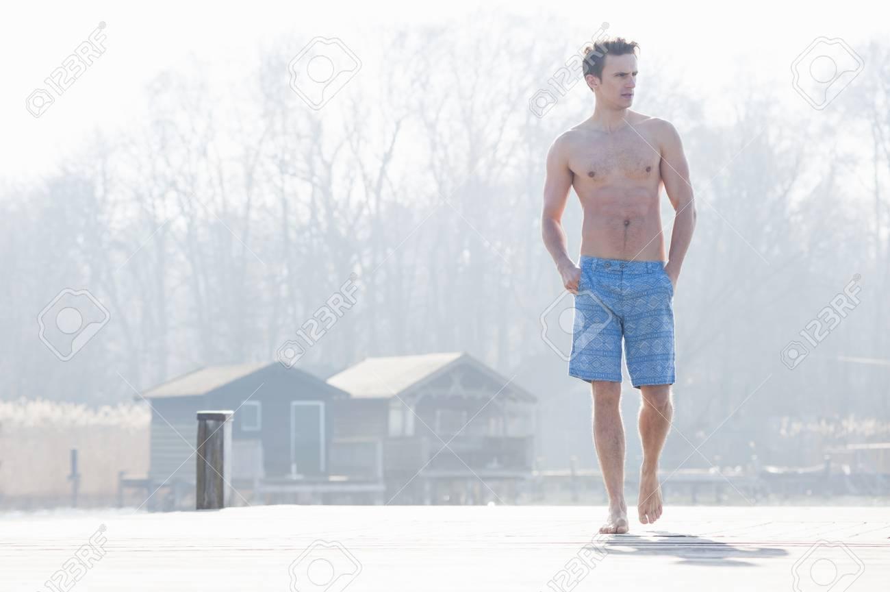 Metà uomo adulto che cammina sul molo indossando pantaloncini da