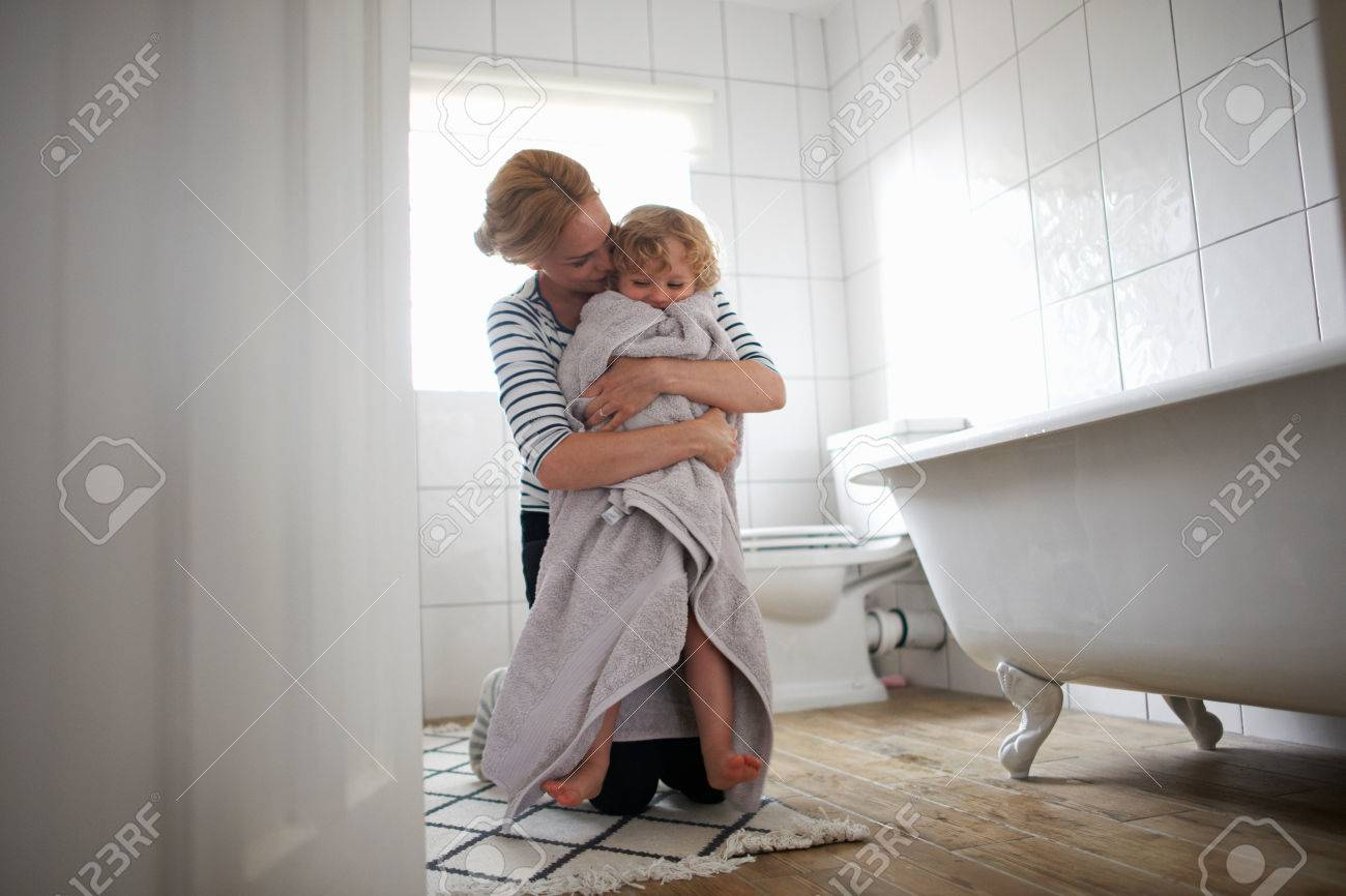 Mother And Daughter In Bathroommother Wrapping Bath Towel Hugging Her Stock