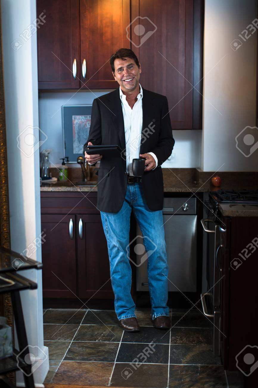 quality design 5a188 5d786 Uomo maturo che indossa giacca e jeans vestito in cucina, tenendo tavoletta  digitale e tazza di caffè, guardando sorridente della fotocamera