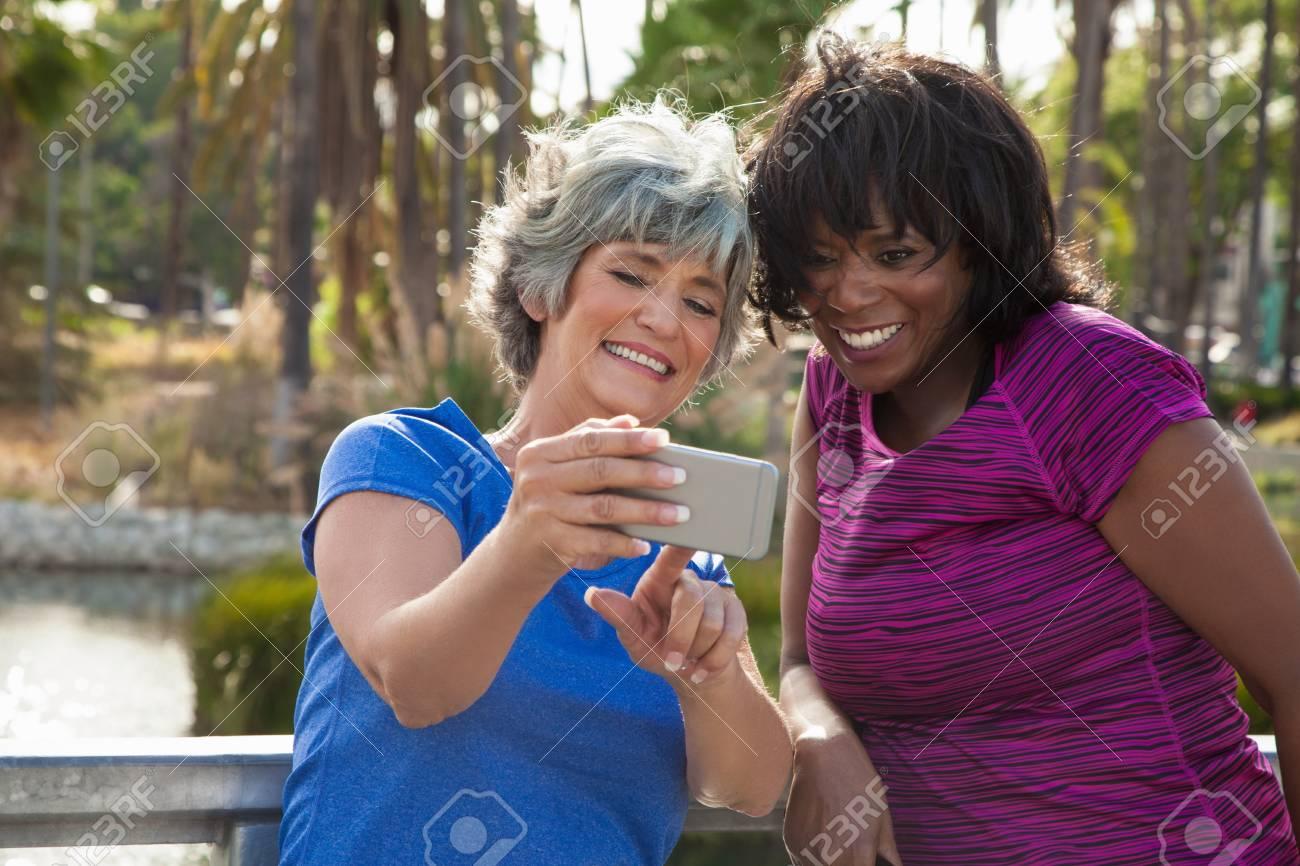 Amigas Maduras maduras amigas en el parque, mirando el teléfono inteligente, riendo