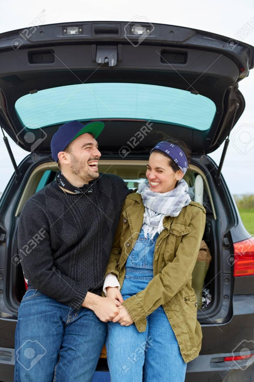 Junge Paare Die Im Offenen Stiefel Des Autos Handchenhalten