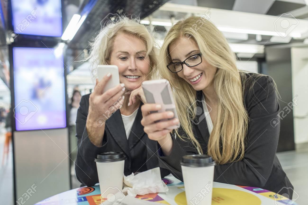 Amigas Maduras dos amigas maduras mirando smartphones en el café del centro comercial