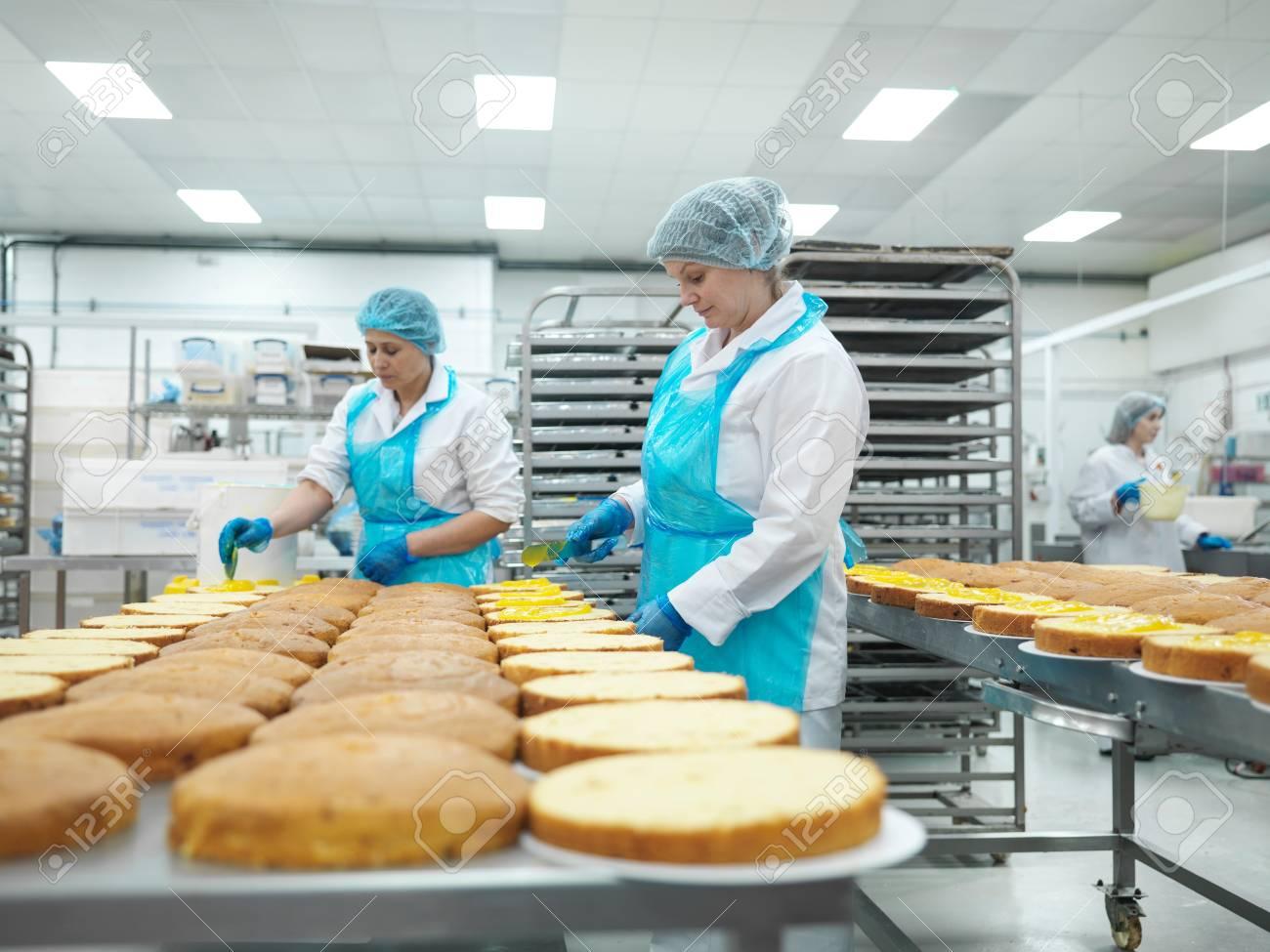 Trabajadoras Extendiendo Relleno En Pasteles En La Fábrica De ...