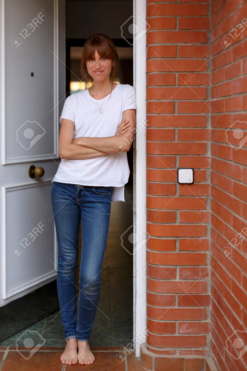 Full length view of mid adult woman leaning against door frame arms crossed Stock Photo & Full Length View Of Mid Adult Woman Leaning Against Door Frame ...