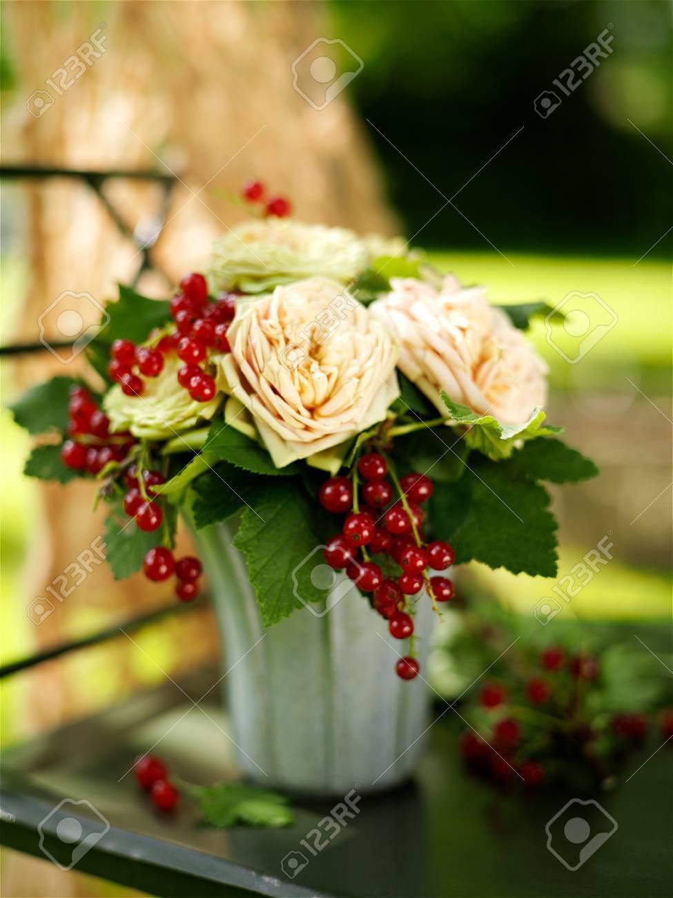 Arreglo Floral De Rosas Y Grosellas En Mesa De Jardín