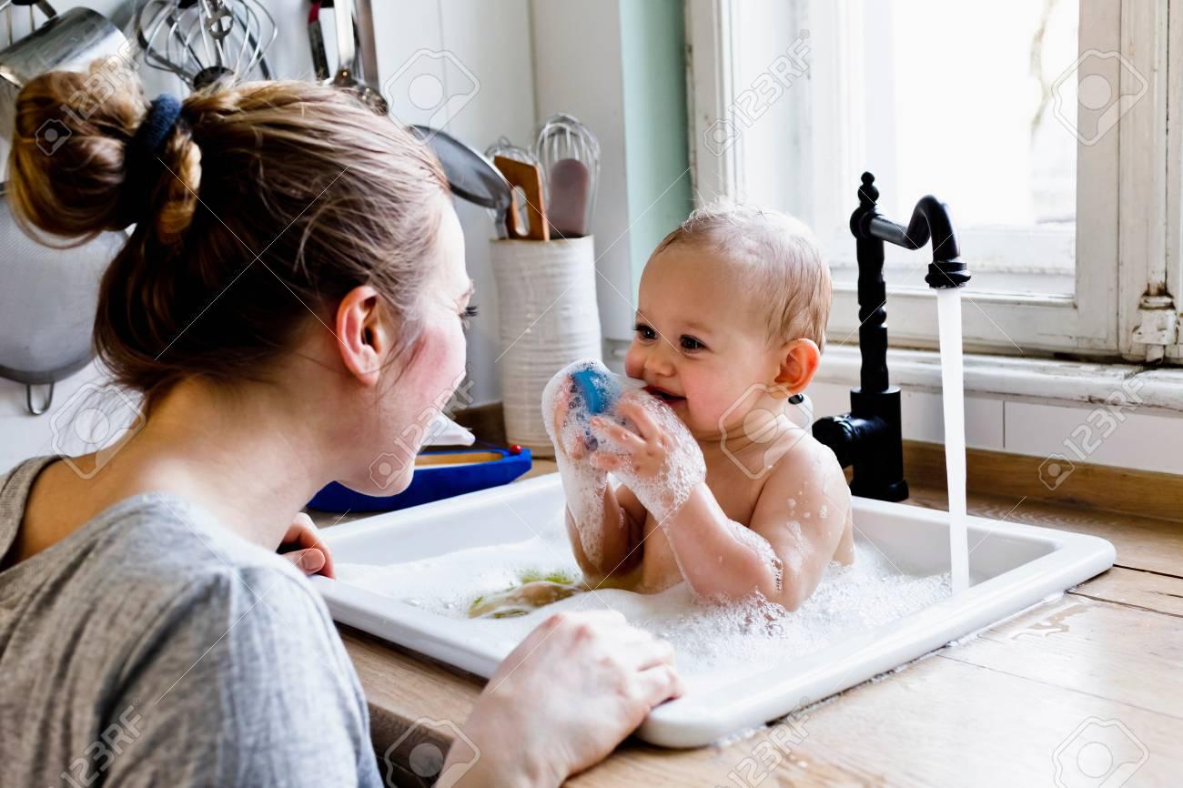 Baby Boy Sucking Sponge Whilst Bathing In Kitchen Sink Stock Photo ...