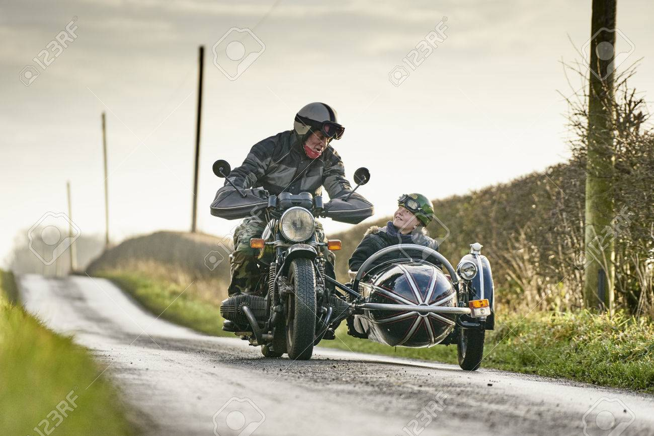 Senior man and grandson riding motorcycle and sidecar along rural road Standard-Bild - 87367346