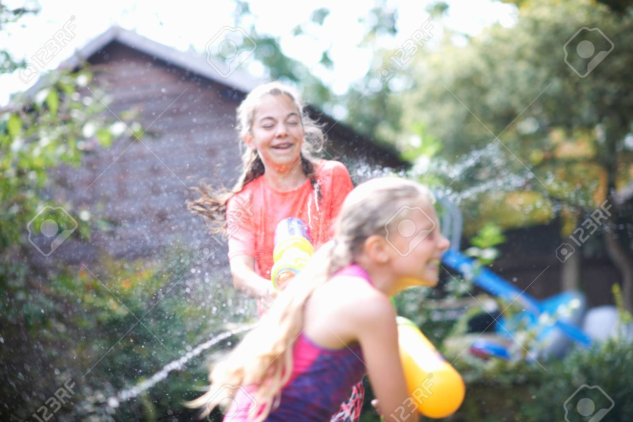 Stock Photo - Teenage girl and her sister squirting water guns at each other  in garden