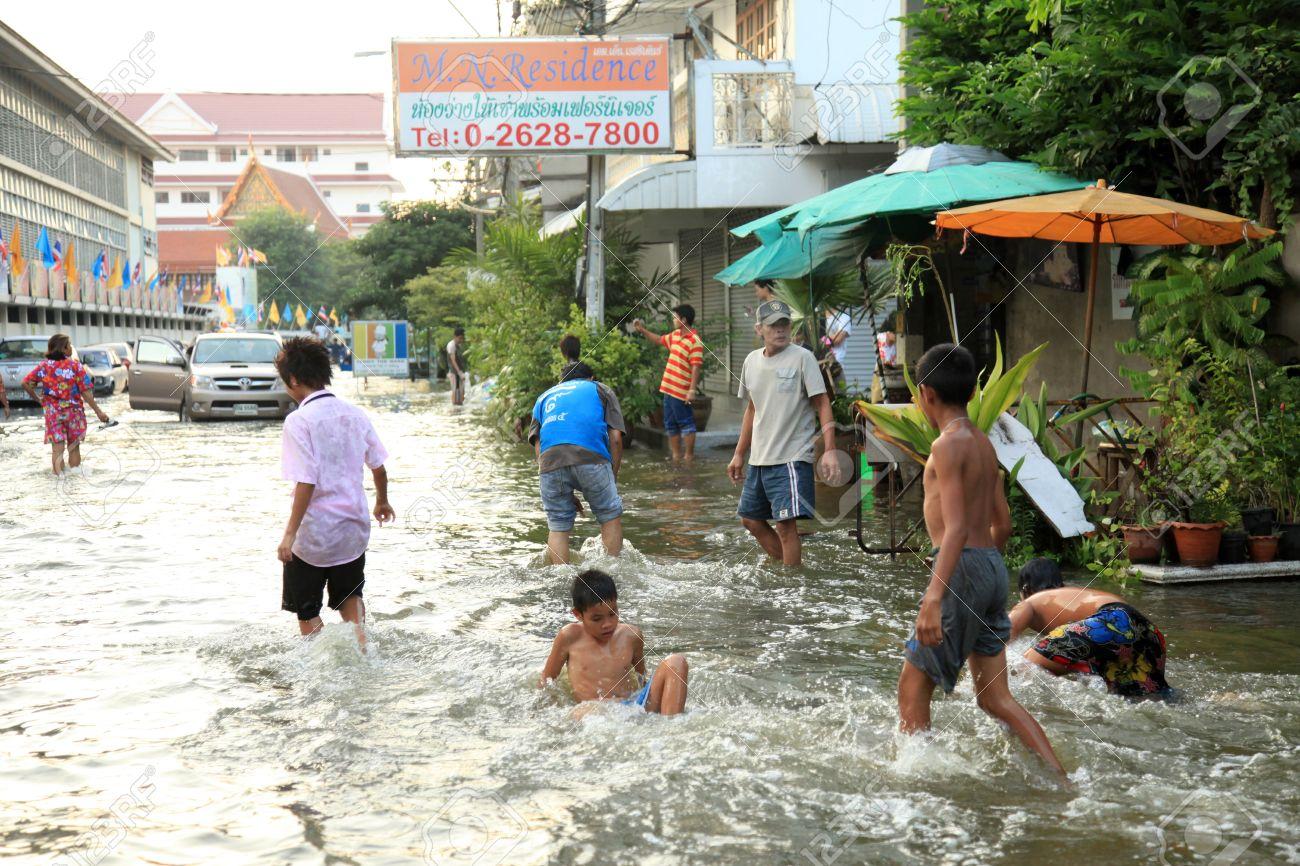 bangkok, thailand - november 17 : kids playing in flood water
