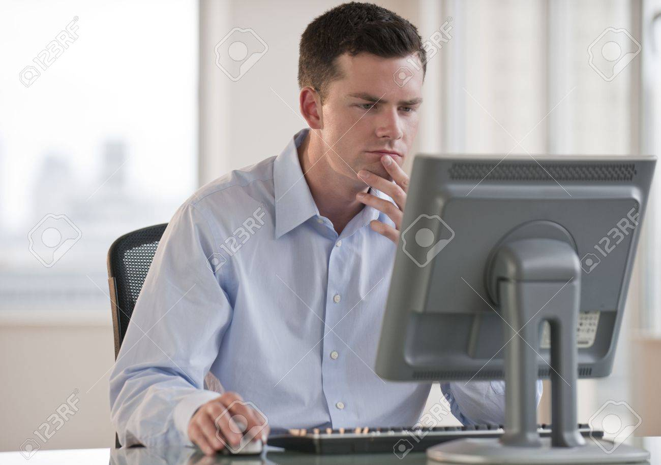 A Businessman Is Working On A Computer. He Is Looking At The ...