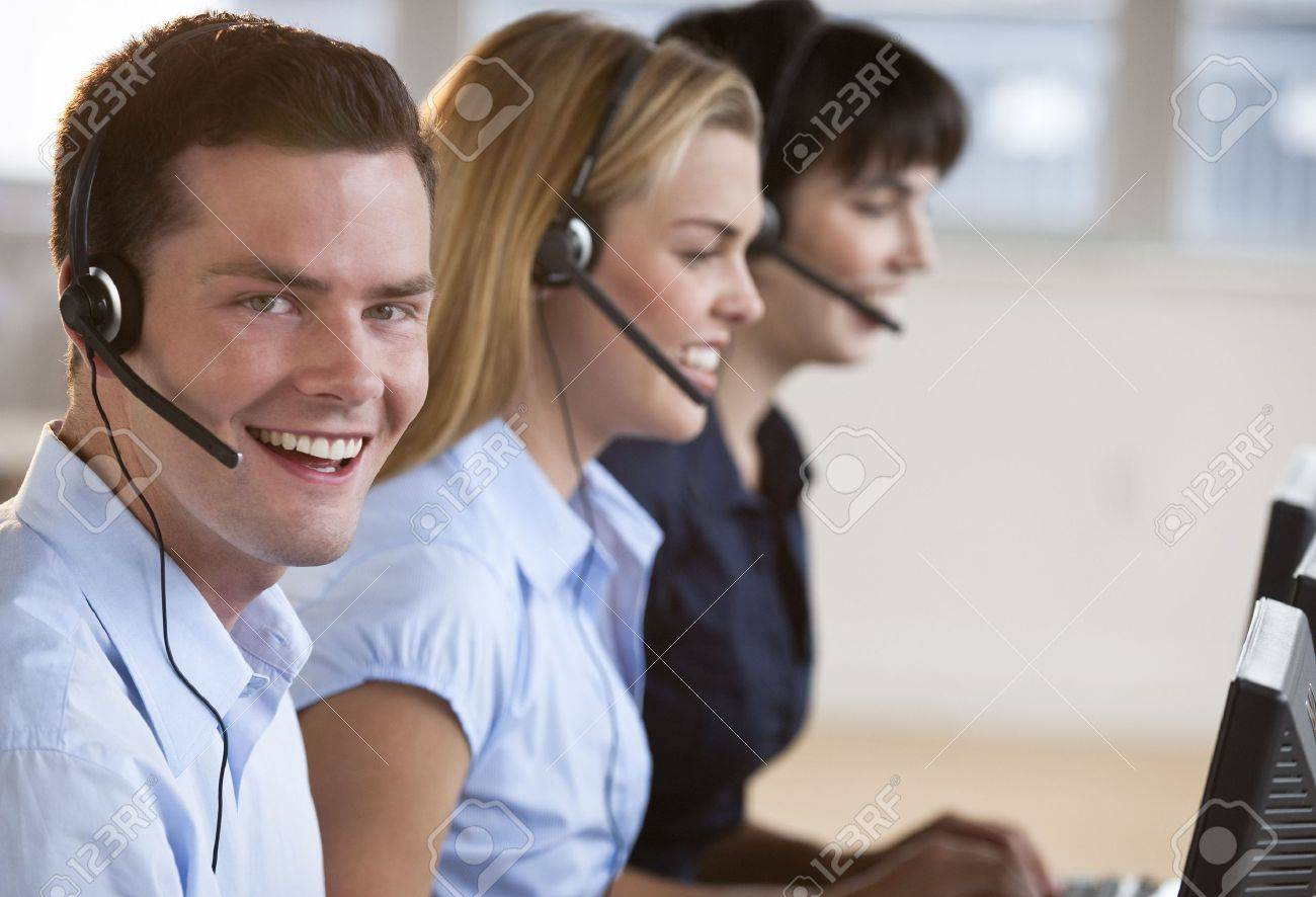 two female and one male customer service representatives smiling stock photo two female and one male customer service representatives smiling they are working on computers and are wearing headsets