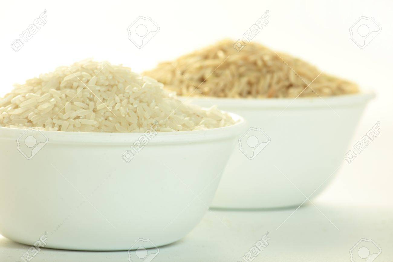 raw white rice in a bowl, bowl of brown rice out of focus Stock Photo - 10099911