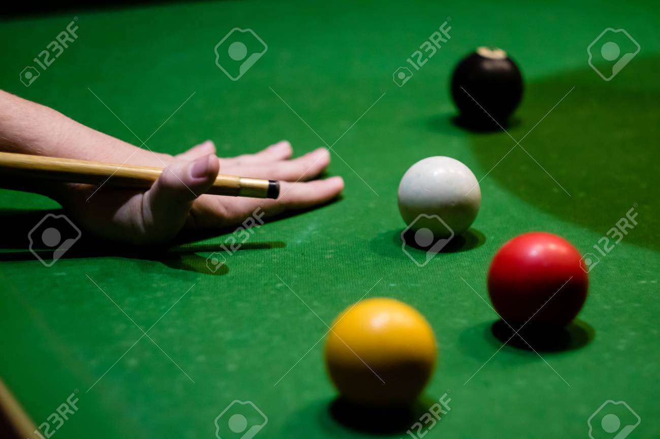 A hand preparing to play a pool shot, with a red and yellow ball,