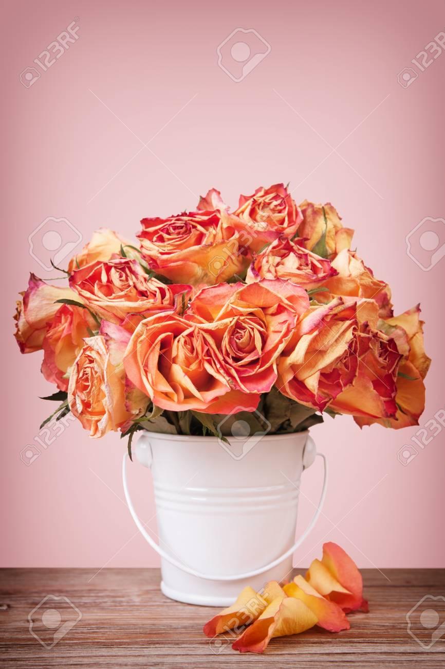 un bouquet de roses anciennes dans un pot en métal blanc sur la