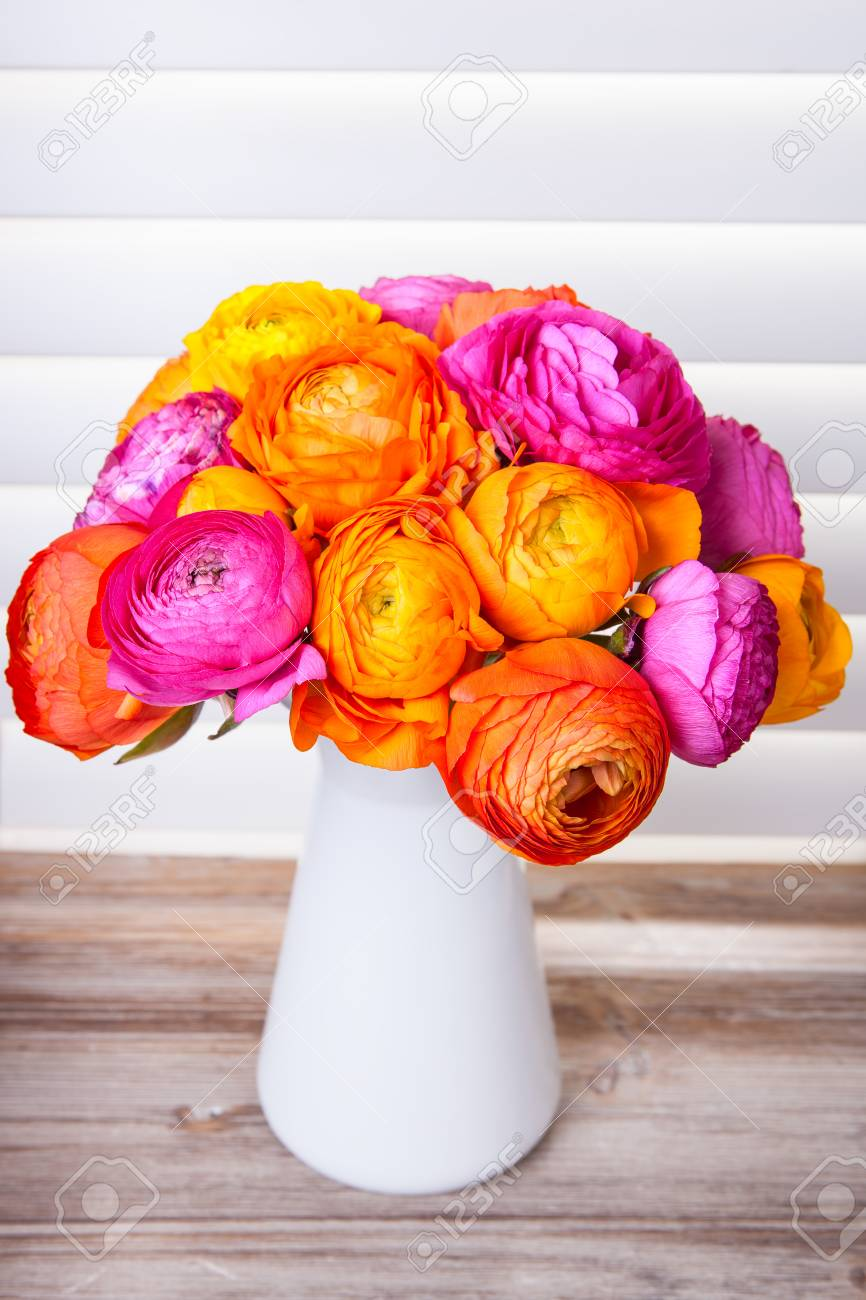 Flowers in a vase on wooden table with sun light coming out of window blinds Stock Photo - 22983934